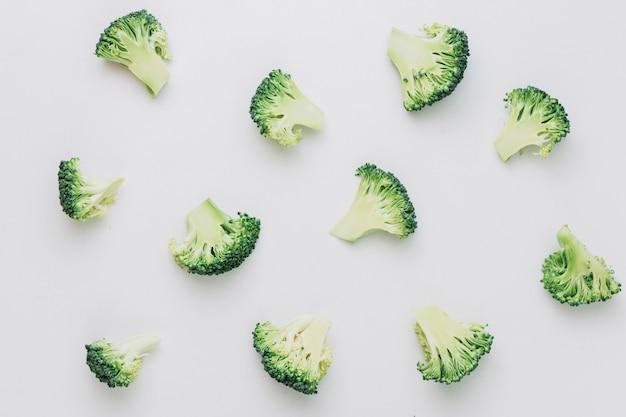 Patroon van gehalveerde gesneden broccolistukken op witte achtergrond Gratis Foto