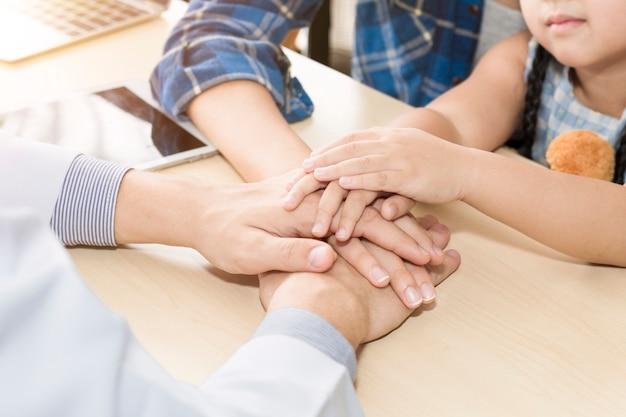 Pediater (arts) man handen samen, geruststellend en bespreken kind op een operatie Premium Foto