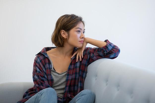 Peinzend aziatisch meisje die op laag over problemen denken Gratis Foto