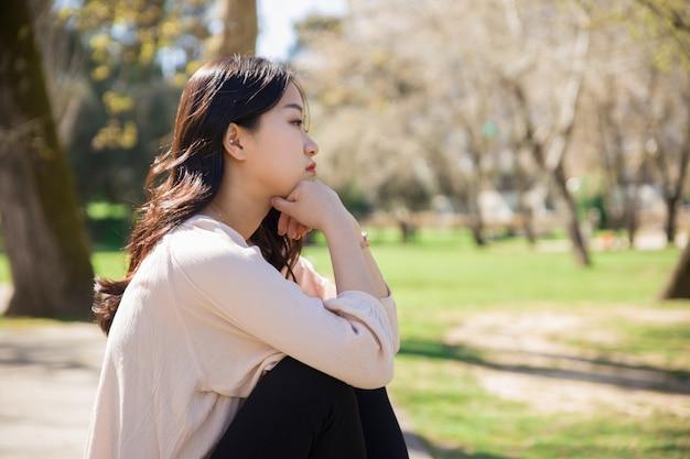 Peinzend droevig aziatisch meisje die blauw in de lentepark krijgen Gratis Foto