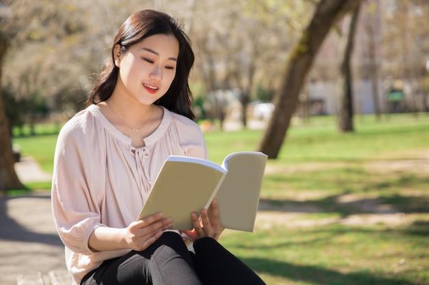 Peinzend glimlachend universiteitsmeisje dat studieboek bestudeert Gratis Foto