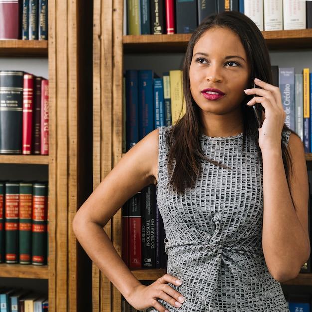 Peinzende afrikaanse amerikaanse jonge dame die op smartphone dichtbij boeken spreekt Gratis Foto