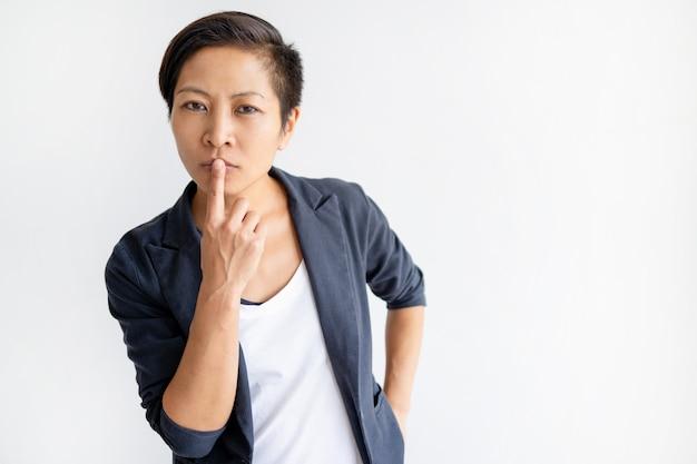 peinzende aziatische vrouw wat betreft mond met vinger