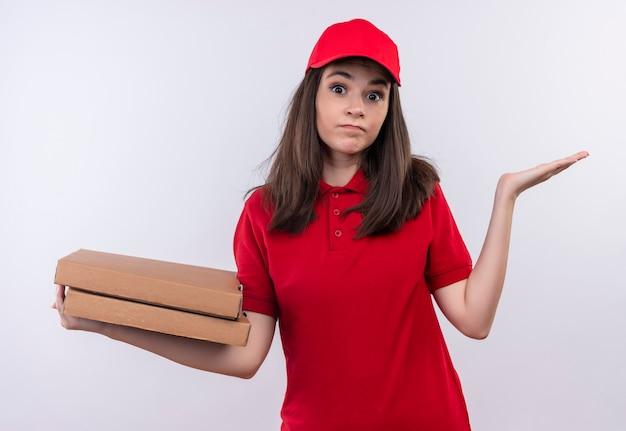Peinzende jonge leveringsvrouw die rode t-shirt in rood glb draagt die een pizzadoos op geïsoleerde witte muur houdt Gratis Foto