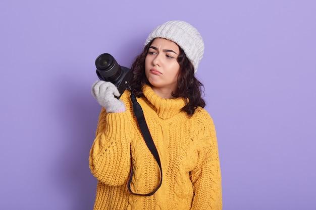 Peinzende jonge vrij europese meisjesfotograaf die moderne camera met behulp van Gratis Foto