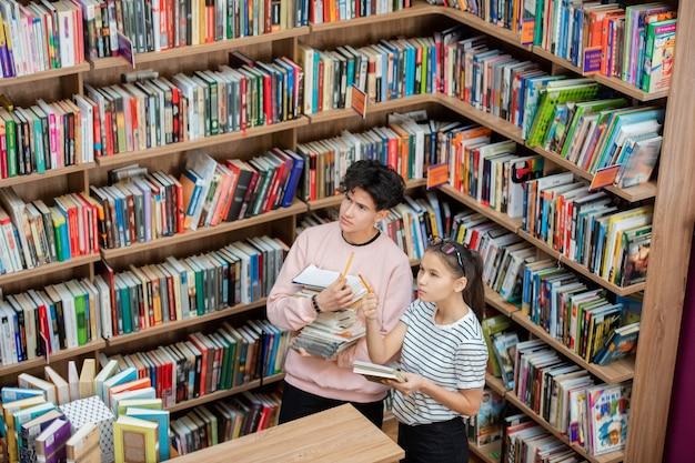 Peinzende man en zijn slimme klasgenoot kijken naar grote boekenplank in de universiteitsbibliotheek terwijl het meisje naar een van de boeken wijst Premium Foto