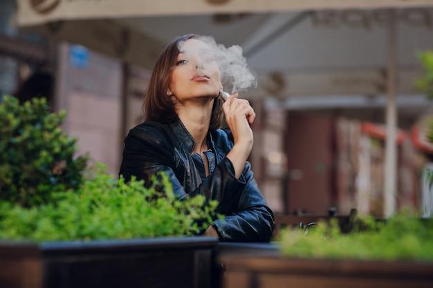 Peinzende vrouw roken in de straat Gratis Foto