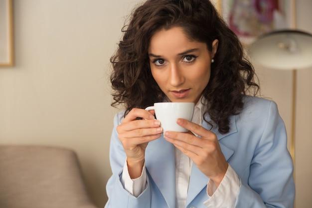 Peinzende vrouwelijke professionele koffie thuis drinken Gratis Foto