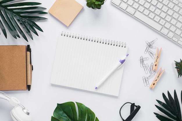 Pen en lege spiraalvormige die blocnote met bureaustkantoorbranche wordt omringd op wit bureau Gratis Foto