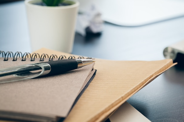 Pen en notitieblok van dichtbij op een bureau Premium Foto