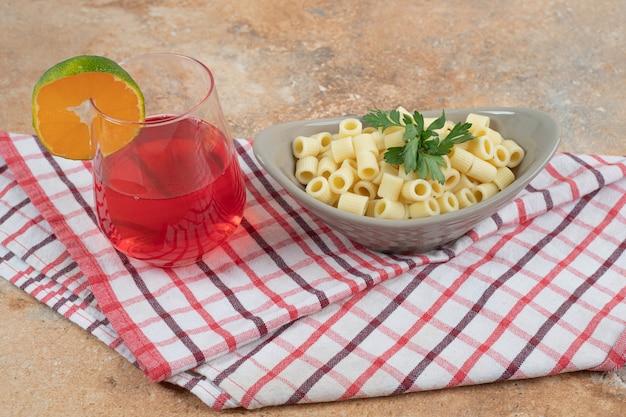 Penne pasta en glas rode cocktail op tafellaken Gratis Foto
