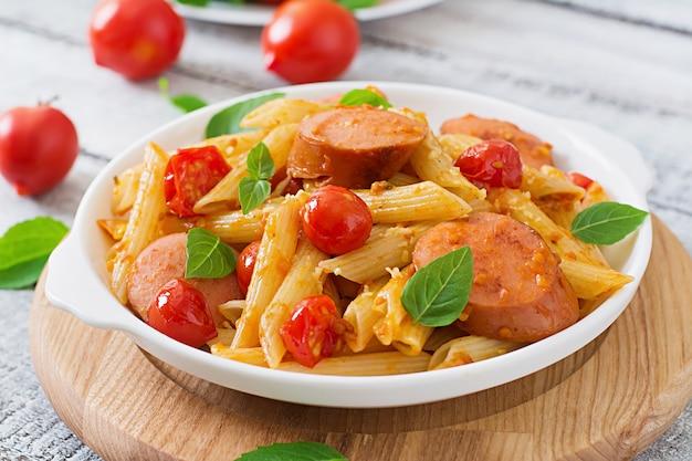 Penne pasta met tomatensaus met worst, tomaten, groene basilicum ingericht in een koekenpan op een houten tafel Gratis Foto