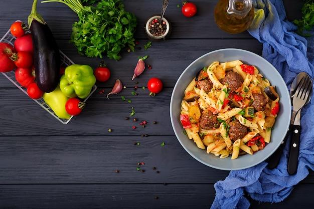 Pennedeegwaren met gehaktballetjes in tomatensaus en groenten in kom Premium Foto