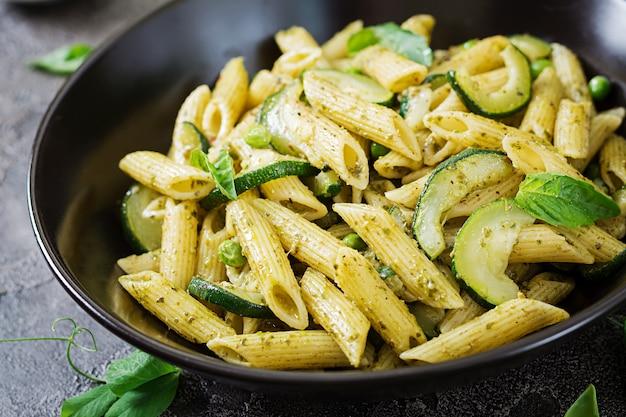 Pennedeegwaren met pestosaus, courgette, groene erwten en basilicum. italiaans eten. Gratis Foto