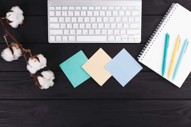 Pennen in de buurt van notebook, takje, papieren en toetsenbord Gratis Foto