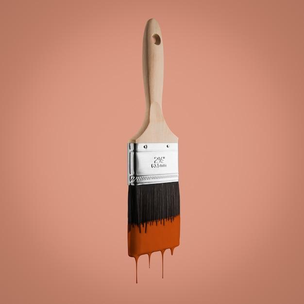 Penseel dat met bruine kleur wordt geladen die van de varkenshaar druipt die - op bruine achtergrond wordt geïsoleerd. Premium Foto