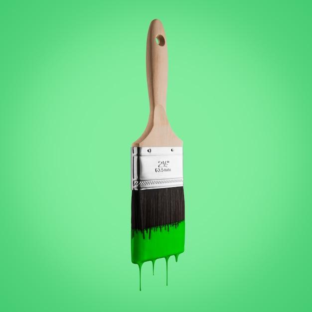 Penseel dat met groene kleur wordt geladen die van de varkenshaar druipt die - op groene achtergrond wordt geïsoleerd. Premium Foto