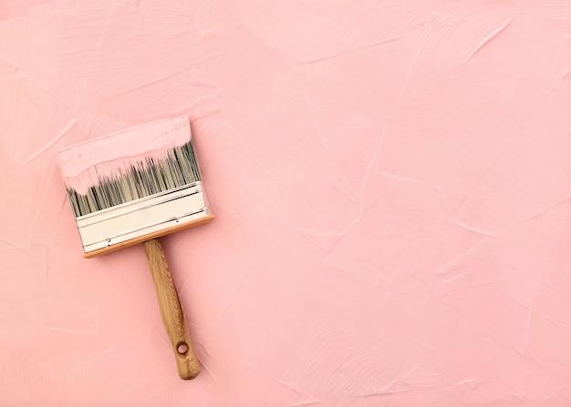 Penseel op roze achtergrond met pas geverfde textuur Gratis Foto