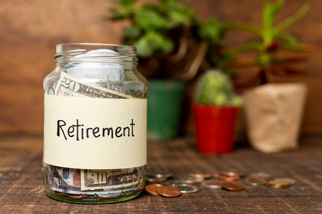 Pensioenetiket op een kruik met geld en installaties op achtergrond wordt gevuld die Gratis Foto