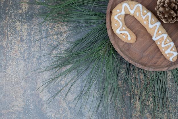 Peperkoekkoekje en dennenappel op houten plaat. hoge kwaliteit foto Gratis Foto