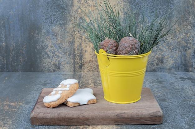 Peperkoekkoekjes en dennenappels op een houten bord. hoge kwaliteit foto Gratis Foto