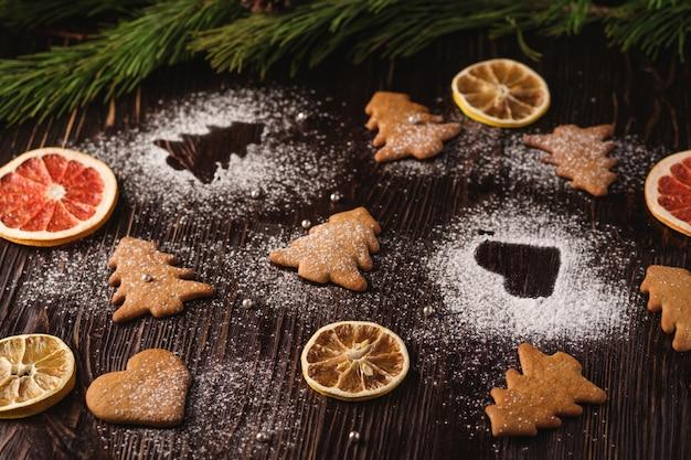 Peperkoekkoekjes in kerstboom en hartvorm, poedersuiker op houten tafel, citrus gedroogd fruit, sparrentak, hoekmening, selectieve aandacht Premium Foto