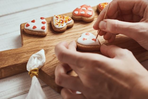 Peperkoekkoekjes versieren met suikerglazuur. de vrouwenhanden verfraaien koekjes in vorm van hart, close-up Premium Foto