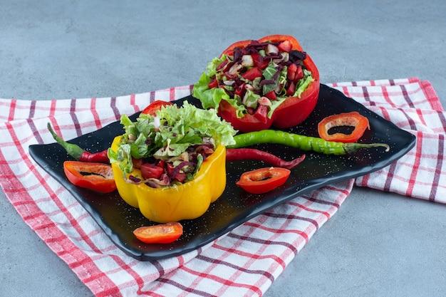 Peperschotel met kleine salade porties op marmeren tafel. Gratis Foto