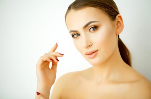 Perfecte jonge model vrouw met een gezonde huid, glanzend haar en gemanicuurde handen. concept voor jonge schoonheid, gezichtsbehandeling en cosmetologie Premium Foto