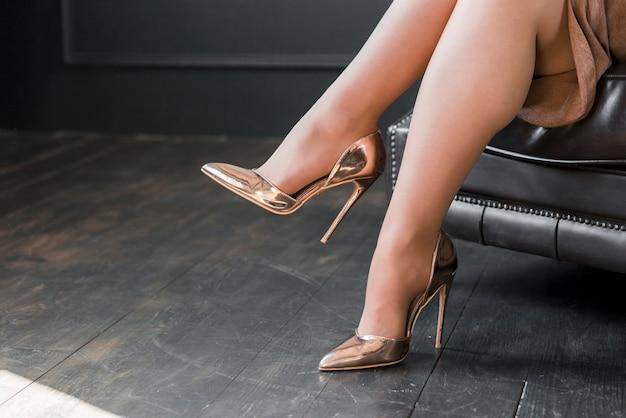 Perfecte vrouwelijke benen die gouden hoge hielen dragen die op bank zitten Gratis Foto
