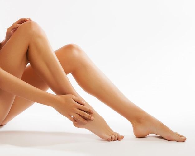 Perfecte vrouwelijke benen, die op witte achtergrond worden geïsoleerd Premium Foto