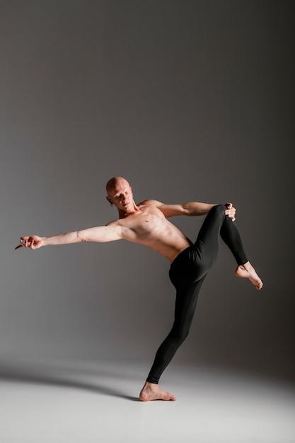 Performer die zijn knie volledig schot houdt Gratis Foto