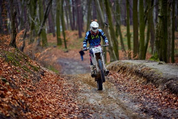 Personenvervoer een motorfiets snel in de herfstbos. Premium Foto
