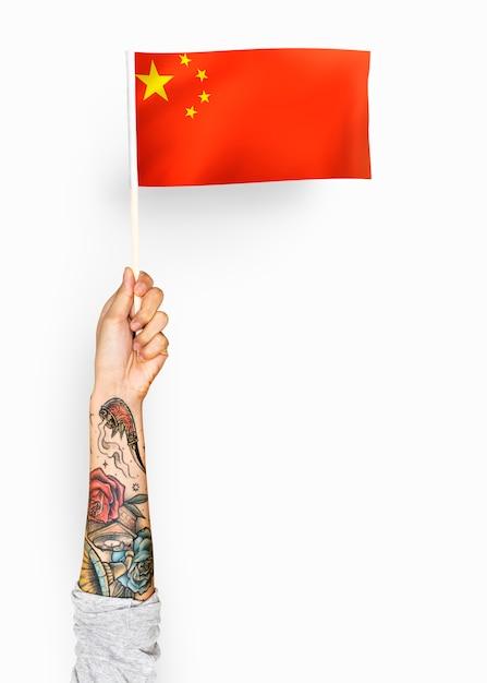 Persoon die de vlag van de volksrepubliek china zwaait Gratis Foto