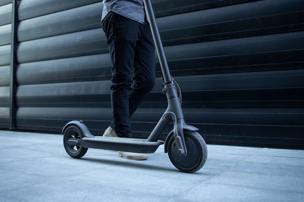 Persoon die door zijn elektrische scooter loopt Gratis Foto
