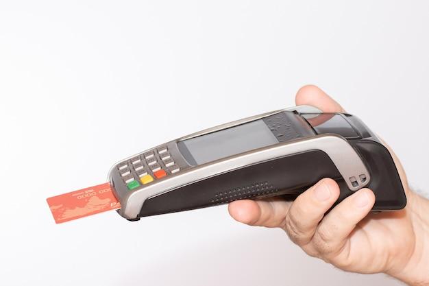 Persoon die een betaalterminal met een rode creditcard vasthoudt, veegt door de machine Gratis Foto