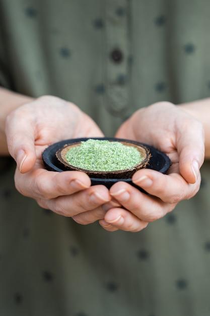 Persoon die een bord met groen poeder vasthoudt dat wordt gebruikt voor rauw veganistisch voedsel Gratis Foto