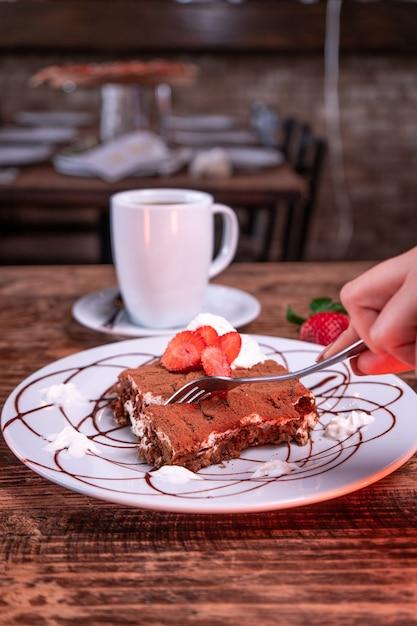 Persoon die een chocoladekoekje met aardbei naast een kop koffie snijdt Gratis Foto