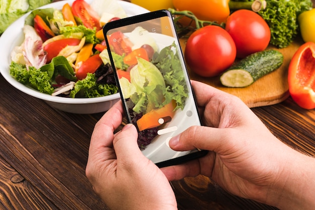 Persoon die een foto van salade neemt Gratis Foto