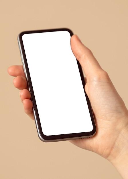 Persoon die een mobiele telefoon van de exemplaarruimte houdt Gratis Foto