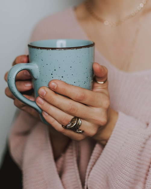 Persoon die een roze sweater draagt die een blauwe mok houdt Gratis Foto