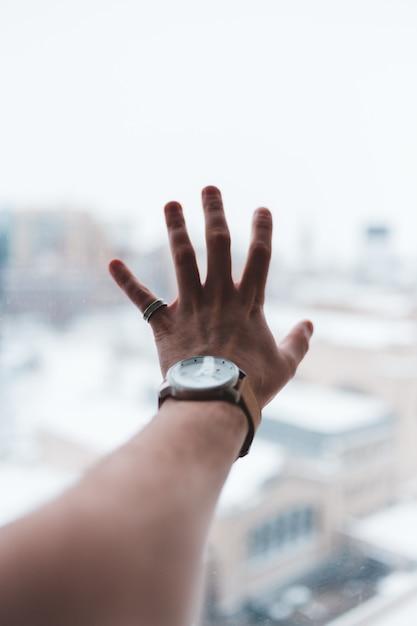 Persoon die een zilveren rond analoog horloge draagt met een zilveren schakelarmband Gratis Foto
