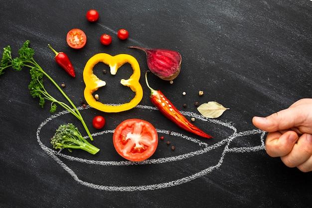 Persoon die groenten op krijtpan koken Gratis Foto