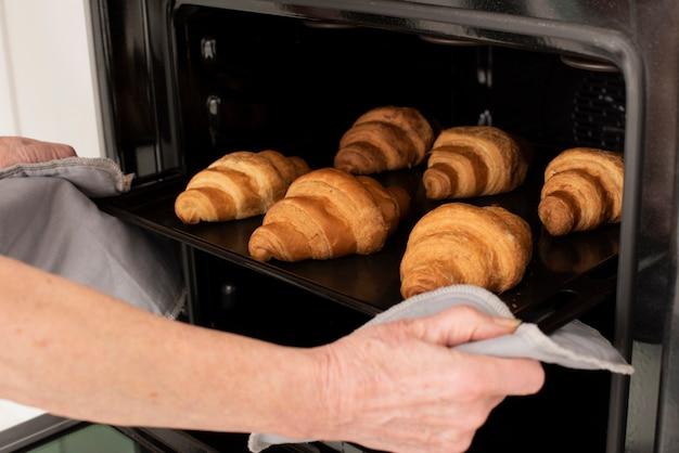 Persoon die het dienblad met croissants in de oven houdt Gratis Foto
