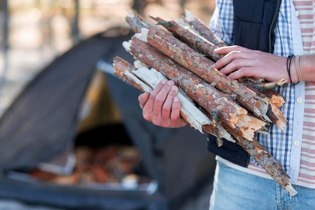Persoon die hout verzamelt voor kampvuur Gratis Foto
