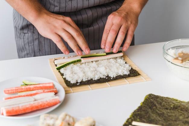 Persoon die ingrediënten toevoegt aan rijst Gratis Foto
