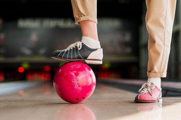 Persoon die met de voet een rode bowlingbal houdt Gratis Foto