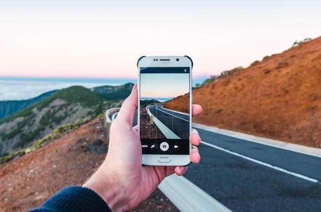 Persoon die met zijn telefoon een foto maakt van een weg op een heuvel - ideaal voor achtergronden Gratis Foto