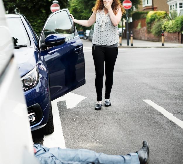 Persoon die op de grond ligt na een auto-ongeluk Gratis Foto