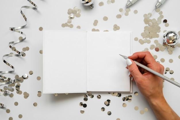 Persoon die op een mock-up papier bovenaanzicht schrijft Gratis Foto